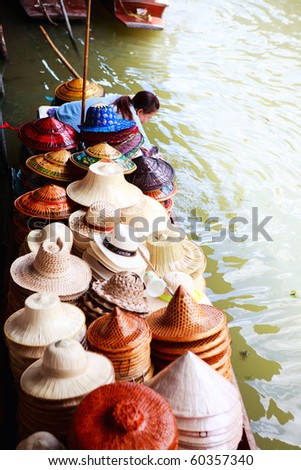 Hat selling on traditional Damnoen Saduak Floating Market near Bangkok in Thailand - stock photo