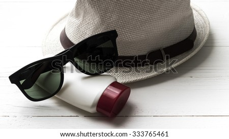 hat sunglasses and body lotion over white table - stock photo