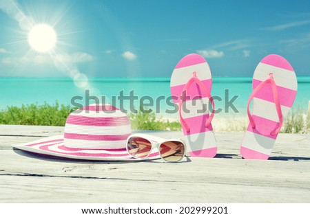Hat, sunglasses and flip-flops against ocean. Exuma, Bahamas - stock photo