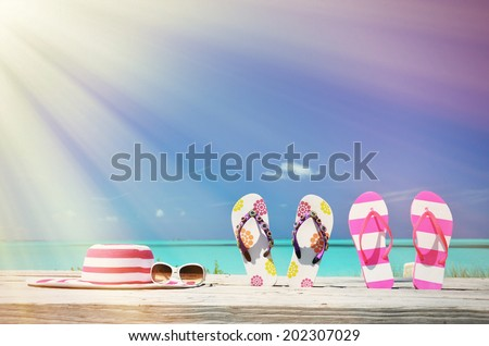 Hat, sunglasses and flip-flops on the beach of Exuma, Bahamas - stock photo