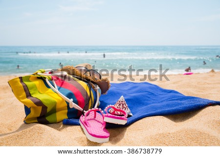 Hat, sunglasses, towel and other items on a tropical beach