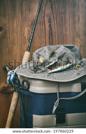 Hat with fishing equipment against wood wall - stock photo