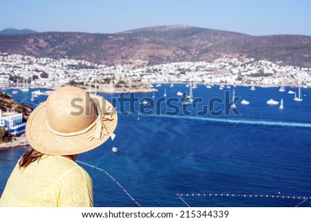 Hat woman is looking to the Bodrum Castle and  marina of Bodrum ,Turkey - stock photo