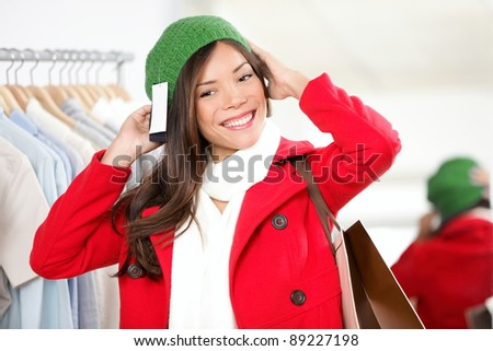 Hat woman. Shopper trying on hat looking in mirror in clothing shop. Beautiful smiling Asian Caucasian female model on shopping trip.