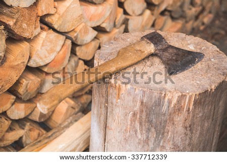 Hatchet on old stump with background of logs.
