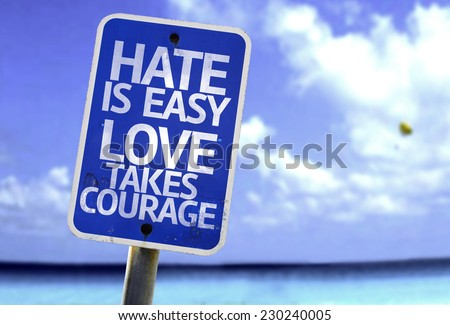 Hate is Easy Love Takes Courage sign with a beach on background - stock photo
