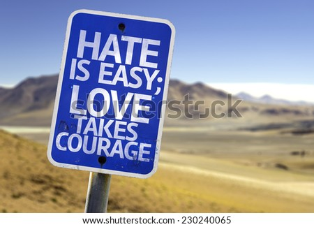 Hate is Easy Love Takes Courage sign with a desert background - stock photo