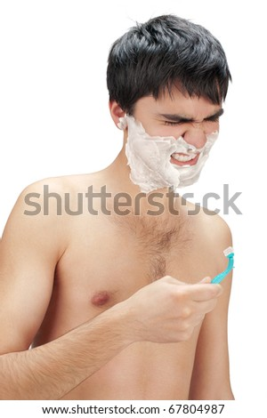 Hate to shave. Young man looking at razor with hate and aggression