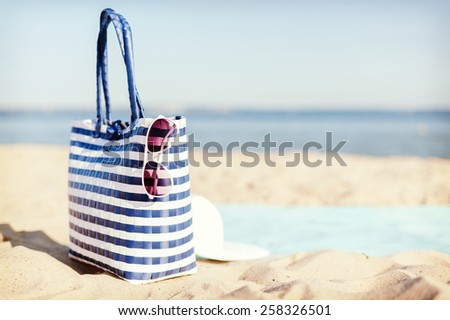 hats and summer concept - white straw hat, sunglasses and bag lying in the sand on the beach - stock photo