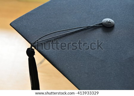 Hats graduates place book on wood background - stock photo