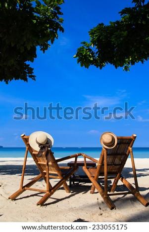 hats on beach chairs of tropical sand beach - stock photo