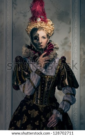 Haughty queen in royal dress with mask - stock photo