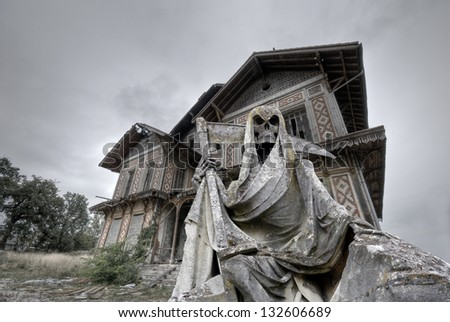 Haunted house. Abandoned and ruined manor with a gream reaper statue in foreground - stock photo