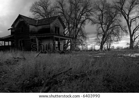 haunted house in rural Wyoming, HDR image processed and converted to monochrome with intentionally added grain for dark, moody look - stock photo