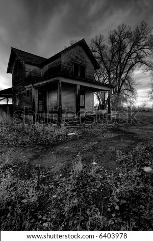 haunted house in rural Wyoming, processed HDR for dark, moody look with intentionally added grain. - stock photo