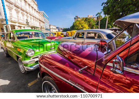 HAVANA-AUGUST 14:Classic vintage cars in front of the Central Park August 14,2012 in Havana.These old cars,the only ones that could be bought until a new law in 2011,are an iconic sight on the city - stock photo