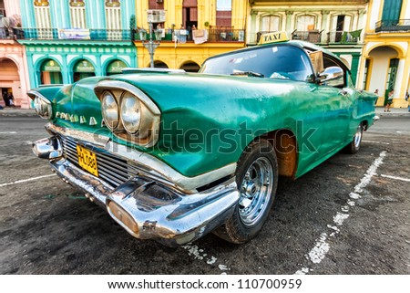 HAVANA-AUGUST 14:Vintage Cadillac in a colorful neighborhood August 14,2012 in Havana.These old cars,the only ones that could be bought until last year,are an iconic sight on the streets of the city - stock photo