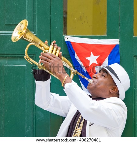 HAVANA,CUBA- APRIL 14,2016 :  Cuban musician playing the trumpet next to a cuban flag at a street in Old Havana - stock photo