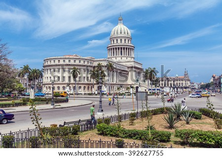 HAVANA, CUBA - APRIL 1, 2012: Heavy traffic with taxi bikes and vintage cars in front of Capitolio