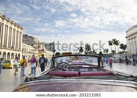 HAVANA, CUBA - DEC 30, 2009: Old vintage american car commonly used as taxi parked in crowded Havana street.  - stock photo