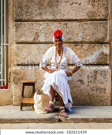 HAVANA, CUBA - DECEMBER 2, 2013: Old black lady dressed in typical cuban clothes smoking a huge cuban cigar next to the Havana Cathedral,  - stock photo