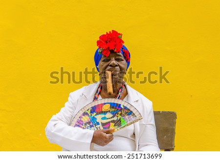HAVANA, CUBA - DECEMBER 2, 2013: Old black lady dressed in typical cuban clothes smoking a huge cuban cigar against yellow wall in Havana. - stock photo
