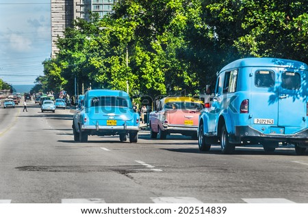 HAVANA, CUBA - DECEMBER 2, 2013: Old classic American cars on the one of Havana streets, where old cars are relic of Cuban revolution and still attracts many tourists.