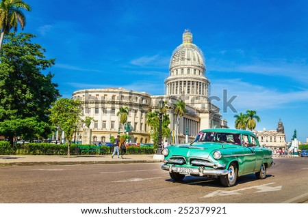 HAVANA, CUBA - DECEMBER 2, 2013: Old classic American grenn car rides in front of the Capitol. Before a new law issued on October 2011, cubans could only trade cars  that were on the road before 1959 - stock photo