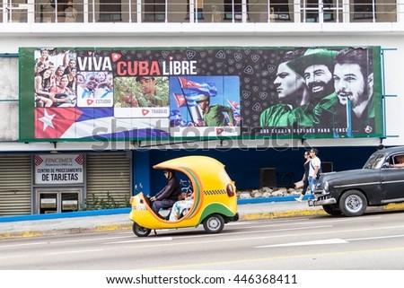 HAVANA, CUBA - FEB 21, 2016: Coco taxi and a propagandistic poster in Vedado neighborhood of Havana. - stock photo