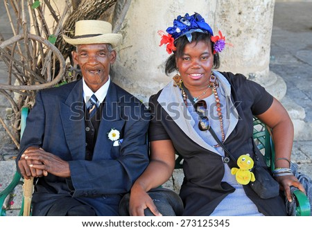 HAVANA, CUBA - FEBRUARY 11:  On February 11, 2012 an old man with a cigar and woman dressed in typical cuban garb pose for the entertainment of tourists in old Havana, Cuba. - stock photo