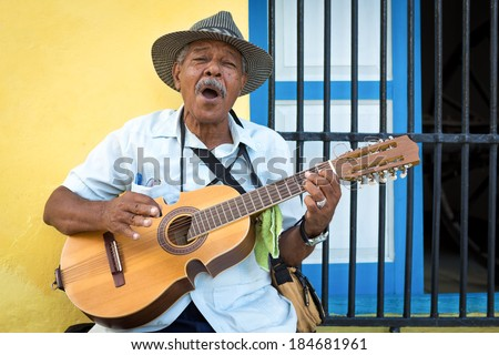 HAVANA, CUBA - FEBRUARY 25, 2014: Street musician playing traditional cuban music on an acoustic guitar for the entertainment of tourists in a typical colorful Old Havana street - stock photo
