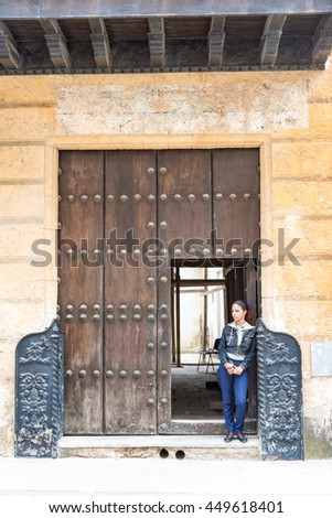 HAVANA,CUBA-FEBRUARY 21,2016: Woman standing at vintage wooden big door. The tropical island of Cuba is known vintage world heritage buildings and structures.