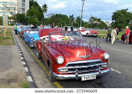 HAVANA, CUBA - JAN 20, 2016:  Tourists check out the many vintage cars being used as taxis at Plaza de la Revolución  (Revolution Square).   - stock photo