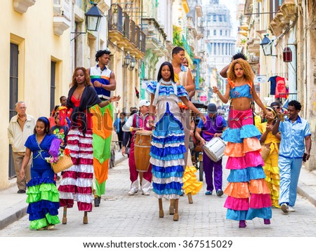 HAVANA,CUBA- JANUARY 24,2015 : Colorful band of musicians and dancers on stilts on a narrow Old Havana street - stock photo