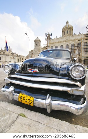 HAVANA, CUBA - JANUARY 28, 2012: Old classic car parked in front of the Revolution museum, formerly Presidential Palace until 1959. - stock photo