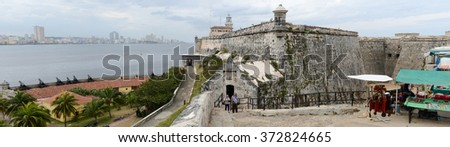 Havana, Cuba - 26 January 2016: People walking and taking picture in front of El Morro fortress with the city of Havana in the background, Cuba - stock photo