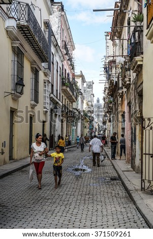 Havana, Cuba - January 5, 2016: Typical scene of one of streets in the center of La Havana - colonial architecture,  and people walking around - stock photo