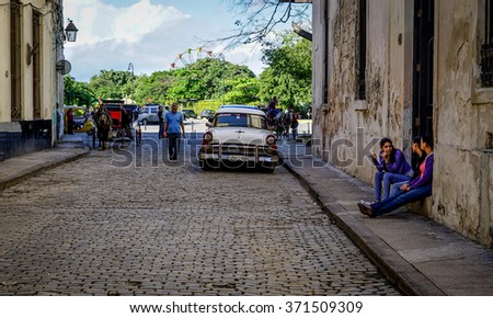 Havana, Cuba - January 5, 2016: Typical scene of one of streets in the center of La Havana - colonial architecture, cars and people walking around - stock photo