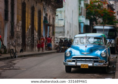 HAVANA, CUBA - JULY 17, 2013: Authentic view of a street of Old Havana with old vintage American car and people on background.