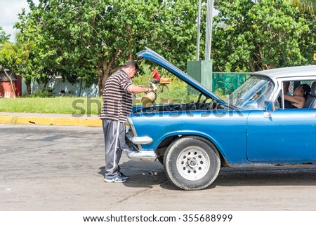 HAVANA,CUBA-JULY 6,2015: Man refilling the radiator of an old American car. The lack of imports have forced Cubans to maintain old cars running.They are the affordable transportation for Cubans