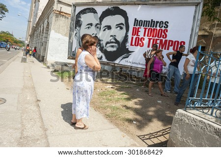 HAVANA, CUBA - JUNE, 2011: Cubans line up in front of a billboard of propaganda featuring slogans and revolutionary leaders. - stock photo