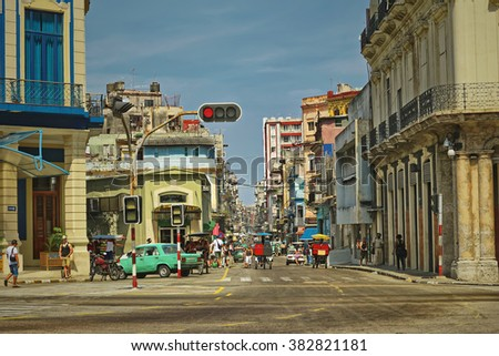HAVANA,CUBA-JUNE 2,2015: People and American vintage cars in the streets of Havana. Vintage style photo