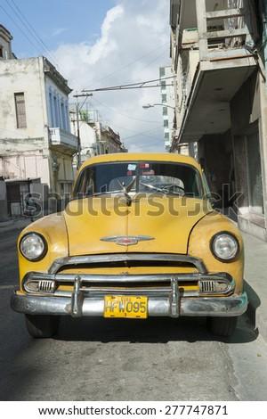 HAVANA, CUBA - JUNE 13, 2011: Vintage yellow American car stands parked on quiet street in Centro, Havana Cuba - stock photo