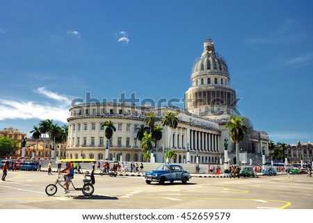 HAVANA, CUBA - May 17, 2016: Hot sunny day in the center of Havana. Cars are riding on the street. Tourists are coming to watch the Capitol.