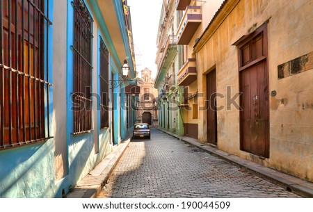 HAVANA, CUBA-MAY 14: Street scene with an old rusty american car on May 14, 2013 in Havana.These vintage cars that can be seen all over the country have become a worldwide known symbol of Cuba  - stock photo