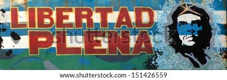 """HAVANA, CUBA-MAY 14: The propaganda poster """"full freedom"""" on a house wall on May 14, 2013 in Havana, Cuba.  - stock photo"""