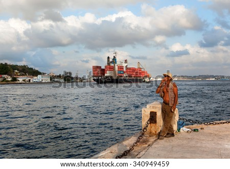 HAVANA, CUBA - MAY 19: Unknown Cuban fisherman catches a fish at the Malecon seawall on May 19, 2013 in Havana, Cuba. Fishing in the city helps to replenish the meager diet of poor people in Havana - stock photo