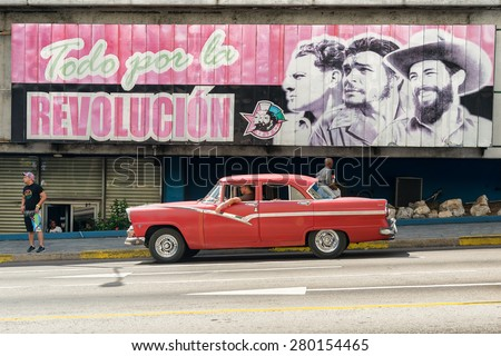 HAVANA,CUBA - MAY 12,2015 :  Vintage american car next to a poster supporting the Cuban Revolution - stock photo