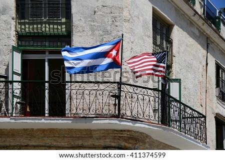 Havana, Cuba. National flag from cuba and USA, in cuba havana. USA and Cuba national flags on house. Havana street and cuba flag. Old house in Havana, with USA and Cuba state flags. Havanna, Cuba.  - stock photo