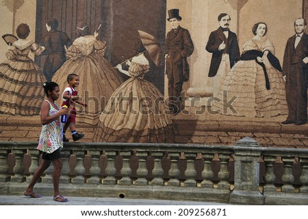 HAVANA, CUBA, - November. 2. 2010: mother and son walking in front of mural near Plaza de Cathedral, a famous touristic landmark in Old Havana, Cuba - stock photo